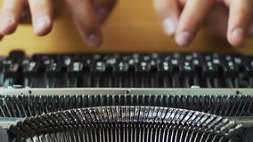 Men`s hands typing an old typewriter. The focus is not on the hands stock video footage