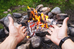 Men`s hands are warming around the fire Royalty Free Stock Photo