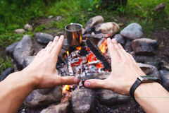Men`s hands are warming around the fire Stock Photography