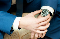 Men`s hands with a watch. A man in a jacket and a white shirt with a watch on his arm Stock Photos