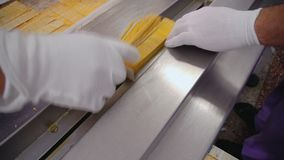 Snack production. Men`s hands in white rubber gloves. Conveyor in the food industry