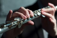 Men`s hands on a wind musical instrument. Playing the flute. Shallow depth of field. Music and sound. Modeling light. stock image