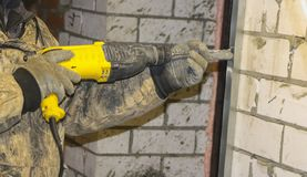 Men`s hands in working gloves, drill hole in steel profiles, to install frame under insulation stock image