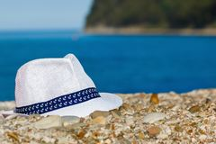 Men`s hat of white color lies on stones against the background of the sea and mountains stock image