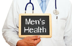 Men's health. Text 'men's health' in white letters on black chalk board  held by doctor or paramedic in white coat with stethoscope, white background Royalty Free Stock Photos