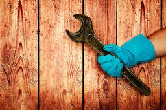 Men`s heavy hand in blue gloves is holding a large old iron key on wooden background royalty free stock photo