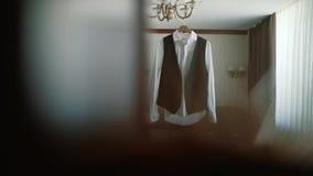 Men`s jacket hanging on the chandelier in room stock video footage