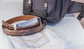 Men's jeans, brown leather belt,  backpack of the photographer Royalty Free Stock Images