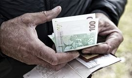 Men`s labor hands of the person counting money. Men`s labor hands of a person counting money holding a passport with documents and the image of the Saint Stock Photos