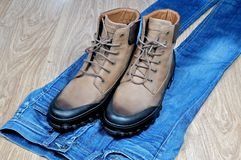 Men`s leather boots on blue jeans royalty free stock image