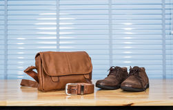 Men`s leather fashion clothing, shoes, bag and belt on plywood t. Able desk in business office room Royalty Free Stock Image