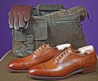 Men`s leather products. Studio shot of men`s oxford shoes weekend bag and gloves Stock Images
