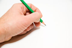 Men's left hand holding a pencil on over white Stock Image