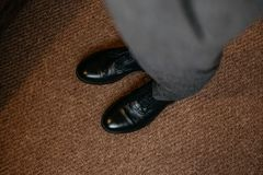 Men`s legs in black patent-leather shoes and gray trousers. View from above. Cropped image Stock Photos