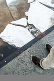 Men`s legs in boots against Ice floes on the river, texture. Danger broken  concept Stock Images