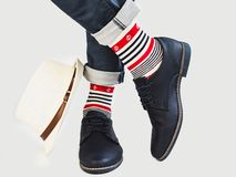 Men`s legs, bright socks, hat and shoes. Men`s legs, bright, multicolored socks with a nautical theme, hat and shoes on a white, isolated background. Concept of stock photos