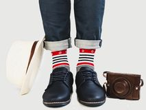 Men`s legs, bright socks, vintage camera, hat and shoes. Men`s legs, bright, multicolored socks with a nautical theme, vintage camera, hat and shoes on a white stock image