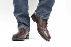 Men`s legs in jeans shod in classic brown Oxford shoes