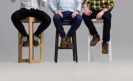 Men& x27;s Legs in Modern Shoes. A Group of Young People Sitting on Chairs without Faces Royalty Free Stock Photography