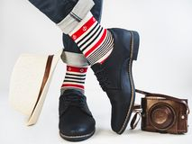 Men`s legs, multicolored socks, vintage camera, hat and shoes stock photos