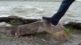 Men`s legs stand on a stone in front of the lake. Flooded stones in the water. Close up of male feet relaxing by the. River. Men`s legs in shoes on the shore of stock video