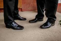 Elegant men`s shoes black worn by the man in black trousers. royalty free stock images