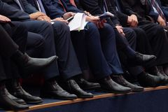 Officials are sitting in the meeting room. Men`s legs in trousers and black shoes. Documents and phones in hand stock image