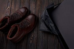 Men`s lether boots on the brown wooden table overhead view. Shoe with shoe box Stock Photo