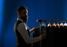 Men`s lothing, shopping in boutiques. Tailor, tailoring. Man suit, tailor in his workshop. Elegant man`s suits hanging stock photos