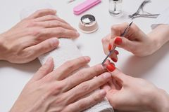 Men`s manicure. hands of the beautician treated cuticle of male hands using pusher, scraper.  royalty free stock photos
