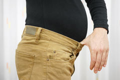 Men's pants are too tight due to the higher weight.  Royalty Free Stock Photos