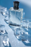 Men`s Perfume in transparent bottle with water droplets and pieces of ice around on blue background. Stock Photography