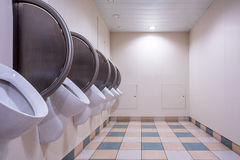 Men`s public restroom with urinals on the wall and checkered floor. Royalty Free Stock Photos