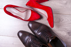 Men`s and red high heel womens shoes on white background. Men`s shoes and red high heel women`s shoes on wooden background. Top view. Copy space for text Stock Images