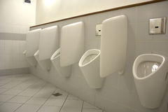 Men's room. With a row of separated urinals Royalty Free Stock Photography