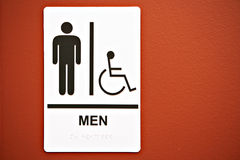 Men's Room Sign on the Wall. Men's Room Sign on on Orange Colored Wall royalty free stock photography