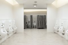 Men`s room urinals discharge ,Toilet bowl in a modern bathroom with bins and toilet paper royalty free stock photos