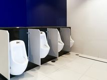 Men`s room urinals discharge of waste from the body,Interior of public clean toilet in shared toilet stock photography