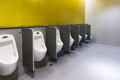 Men`s room urinals discharge of waste from the body stock images