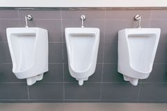 Men`s room with white porcelain urinals in line. Modern clean public toilets with tiles royalty free stock photography