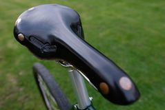 Detailed view of an expensive leather men`s saddle on a retro bicycle royalty free stock photo