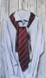 A men`s shirt with a five ties hanging on a hanger on a backgrou Royalty Free Stock Photo