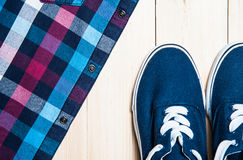 Men's shirt and footwear on a wooden background close up Royalty Free Stock Images