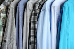 Men`s shirts on hangers, blue, gray and checkered. Men`s shirts on hangers. Blue, gray and checkered Royalty Free Stock Images
