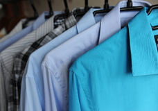 Men`s shirts on hangers, blue, gray and checkered. Men`s shirts on hangers. Blue, gray and checkered Royalty Free Stock Photos