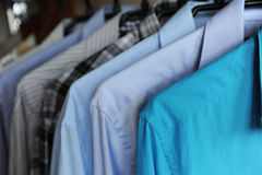 Men`s shirts on hangers, blue, gray and checkered. Men`s shirts on hangers. Blue, gray and checkered Stock Image