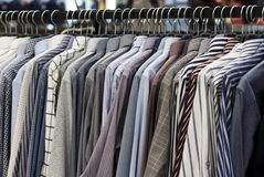 Men`s shirts on hangers in the store, close-up stock images