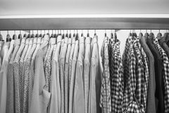 Men`s shirts on the rack, black and white frame.  Stock Photo