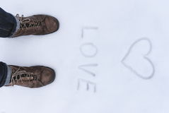 Men's shoe close up view with love simbol wrtien on the snow Stock Image