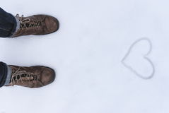 Men's shoe close up view with love simbol wrtien on the snow Stock Photography